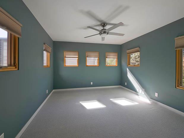 ภาพห้อง ผนังสีเขียว พื้นพรม ติดพัดลมเพดาน
