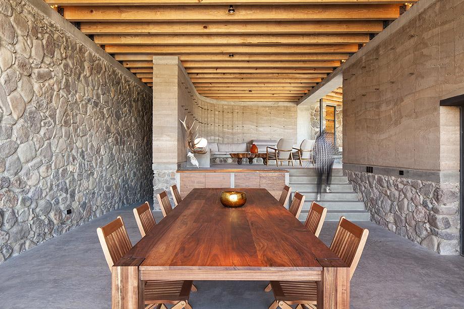 โต๊ะรับประทานอาหารทำจากไม้เพิ่มความนุ่มนวลให้ห้องผนังคอนกรีต
