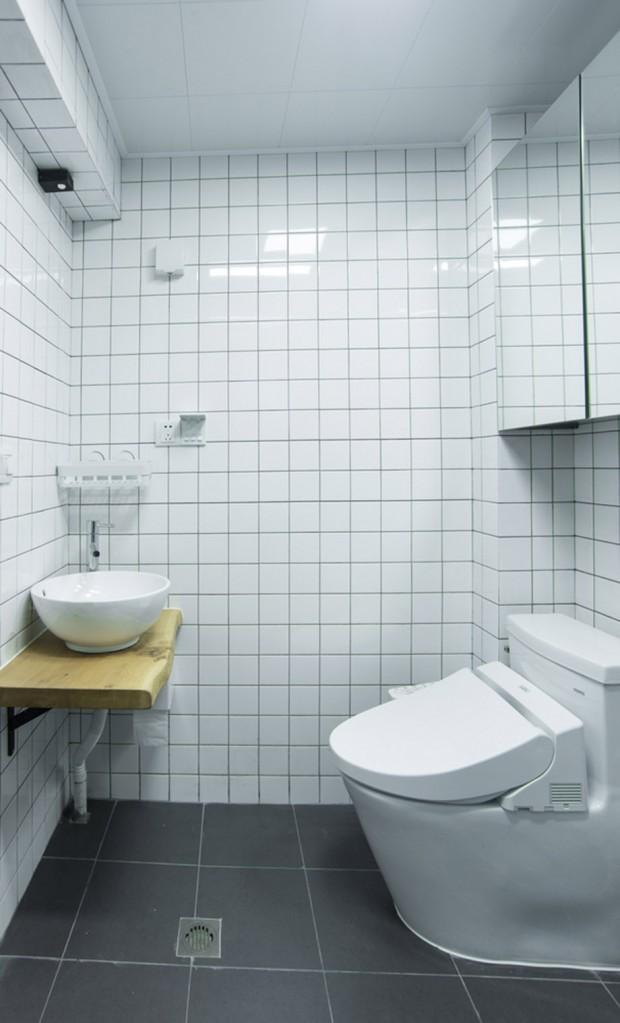 ้ห้องน้ำตกแต่งด้วยกระเบื้องสีขาวและเคาท์เตอร์ไม้