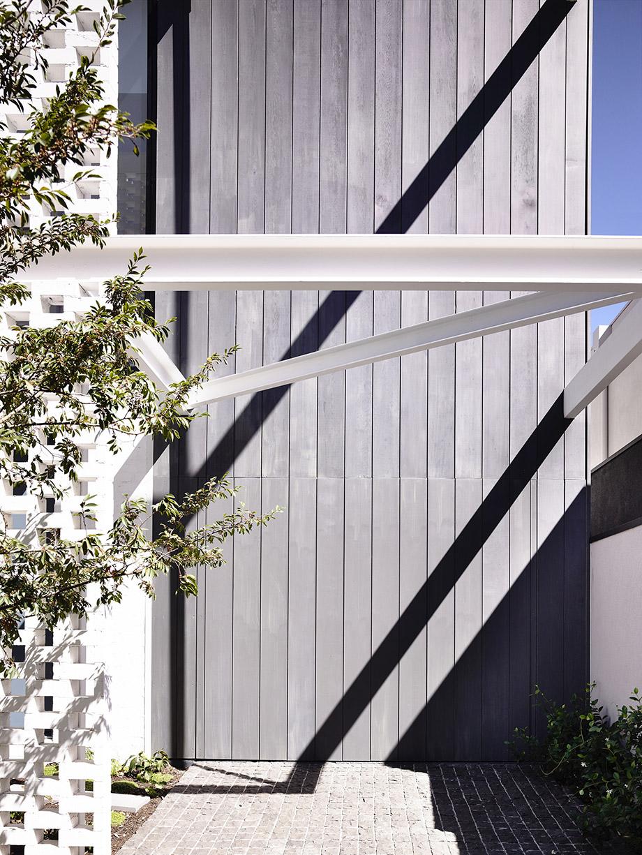 ฟาซาดบ้านสีดำตัดกับเหล็กเส้นสีขาว