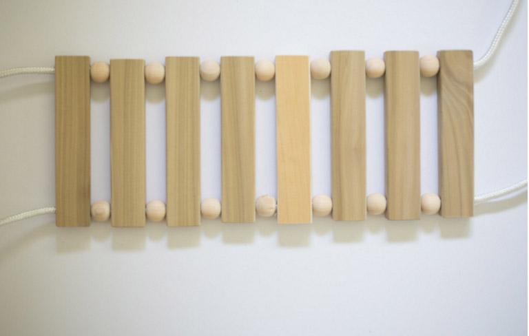 ร้อยไม้แผ่นสี่เหลี่ยมกับไม้กลึงกลมเข้ากับเชือก