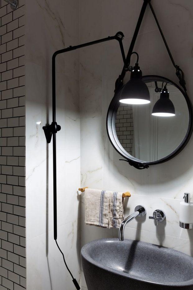 กระจกและโคมไฟสีดำตัดกับผนังสีขาว