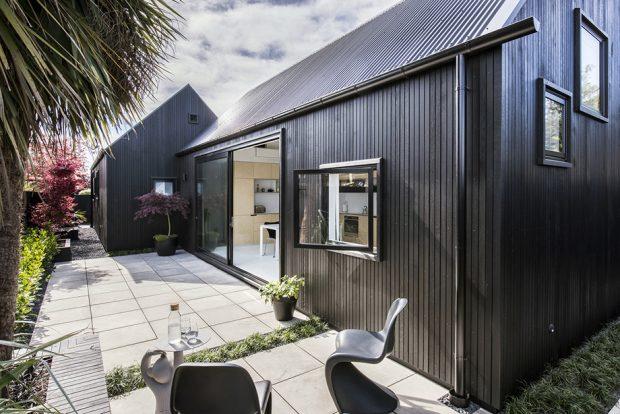 บ้านผนังสีดำเปิดบานสไลด์ได้กว้าง