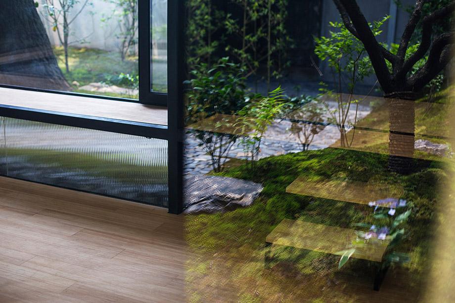ผนังกระจกส่องสะท้อนเงาไม้