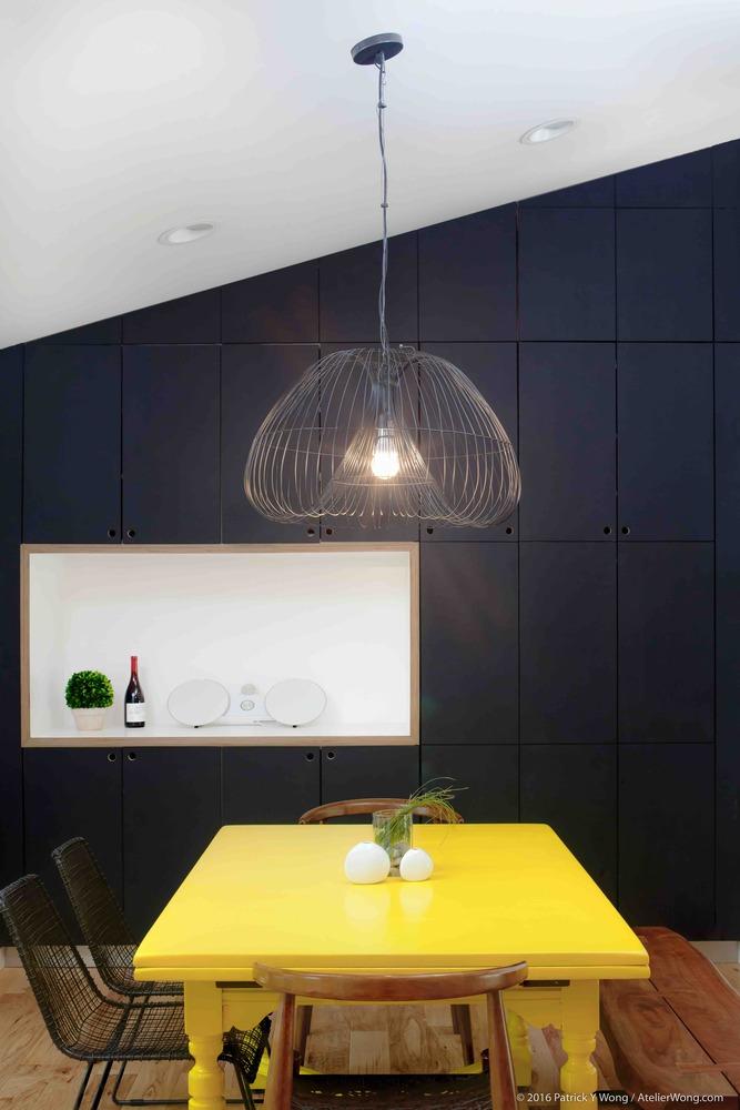 ชุดโต๊ะอาหารสีเหลืองตัดกับผนังห้องสีดำ