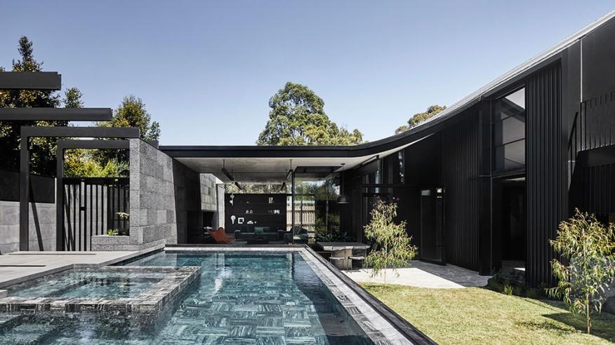 บ้านสีดำมีสนามหญ้าและสระว่ายน้ำ