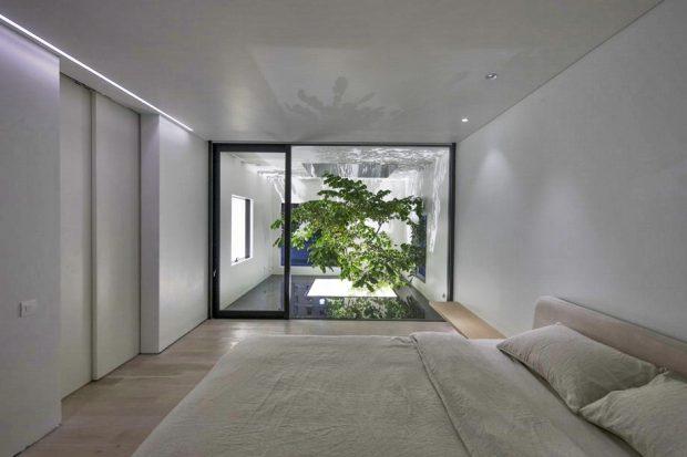 ห้องนอนผนังกระจกเห็นต้นไม้กลางบ้าน