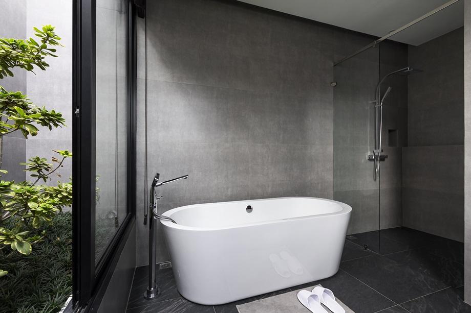 ผนังสีเทาอ่างอาบน้ำสีขาว